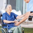 Caretaker Helping Senior Woman To Get Up From Wheelchair — Stock Photo #55489027