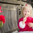 Adorable Little Girl Sitting On Bench with Her Candy Cane — Stock Photo #61437061