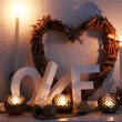 Romantic still life with wicker heart and candle lights on mantelpiece and white wall background — Stock Photo #65347155