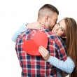 Man kissing beautiful woman with heart card — Stock Photo #64754097