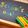 Blackboard with school's out text written in colorful letters over wooden table — Stock Photo #73157377