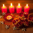 Image of Christmas decorations, candles, gifts on brown background — Stock Photo #59407785