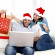 Young attractive Hispanic couple in love online Christmas shopping with computer — Foto Stock #56593321
