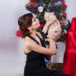Beautiful sexy happy smiling young woman in evening dress with bright makeup with red lipstick, sitting by the Christmas tree with a small kitten in her arms in a festive Christmas evening — Stockfoto #60544463