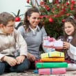 Family exchanging gifts in front of Christmas tree — Stock Photo #58150205