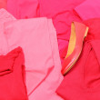 Heap of red and pink clothes with womanly shoes — Stock Photo #58553855