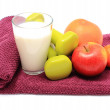 Fresh fruits, glass of milk and dumbbells on purple towel — Stock Photo #64325831