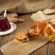 Typical turkish owen product cheese pogaca with wood plate and black tea — Stock Photo #55575929
