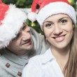 A Christmas Couple wearing Santas Hats. Smiling Family Celebrat — Stock Photo #65226029