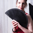 Attractive woman in red dress hiding behind fan — Stock Photo #78362136