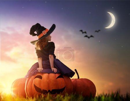 cute little witch with a big pumpkin.