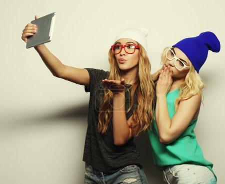 考虑自拍照的两个时髦女孩朋友