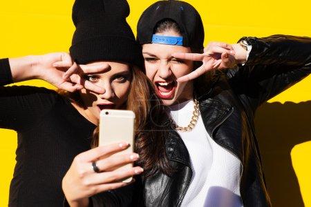 十几岁的女孩朋友在户外使自拍照在电话上