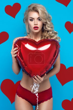 Blond woman with heart balloon
