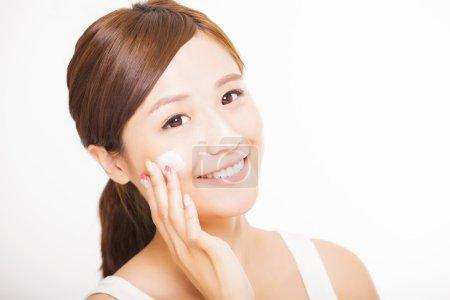 漂亮的年轻女子在脸上涂化妆品霜_高清图片_邑石网