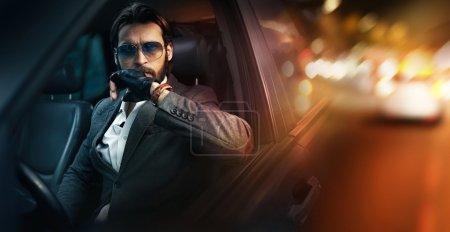 室外肖像的时尚男人驾驶一辆车