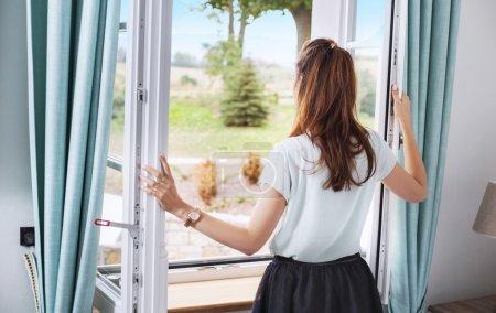 一位优雅的女士打开卧室的窗户