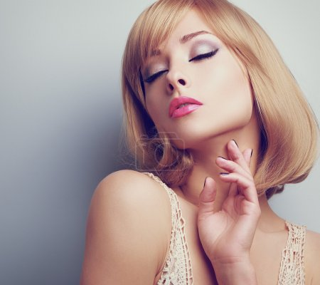 双封闭的化妆眼睛摸脖子的美丽的金发女子