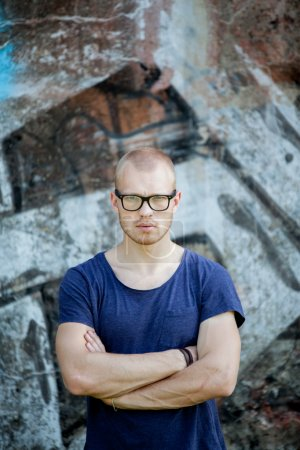 Portrait of the young man in glasses against the background of a concrete wall with graffiti. The guy looks at the camera.