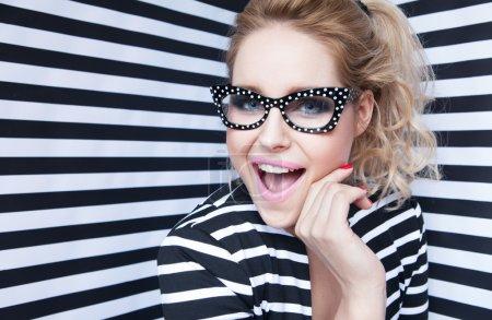 戴眼镜条纹背景上年轻漂亮的金发女人