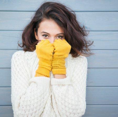 Brunette woman wearing gloves.