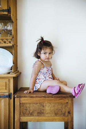 可爱的小女孩坐在木桌上的尾巴_高清图片_邑石网