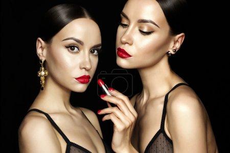 两个美丽年轻女士用红色口红