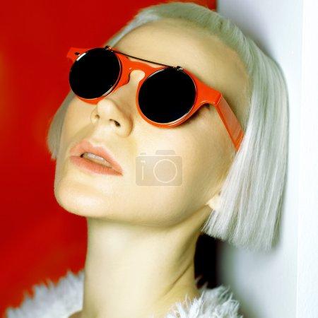 迷人的金发碧眼的时髦发型和时髦的太阳镜