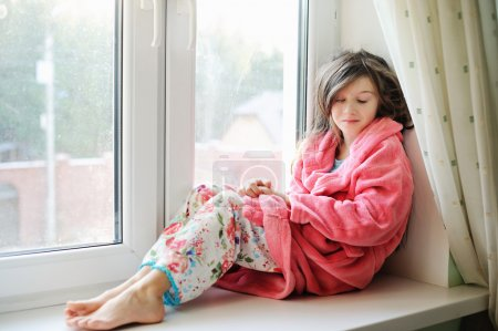 Beautiful little girl in bathrobe near window