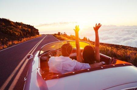 浪漫的情侣在日落时分在美丽的路上行驶