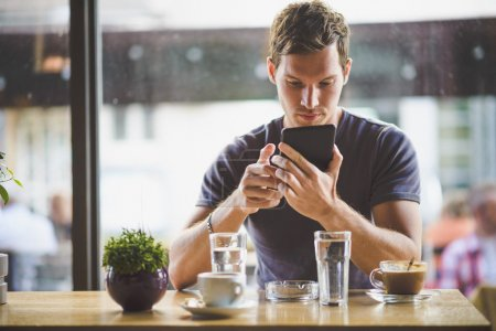 Young man watching tablet in cafe