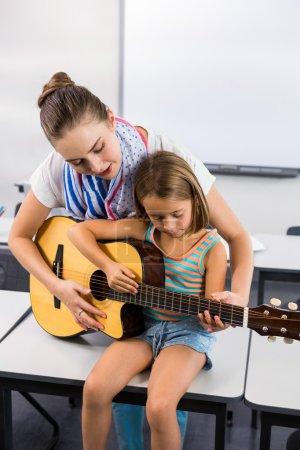 老师协助女孩弹吉他