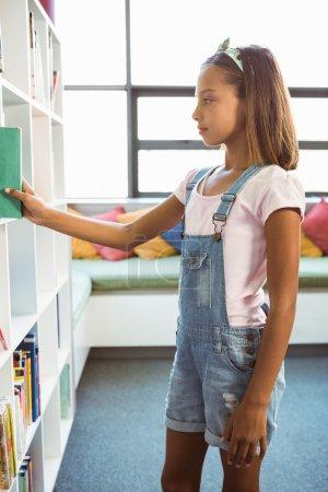 姑娘在图书馆把书从书架上
