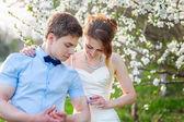 新娘新郎显示他的二头肌上的一棵开花的树背景