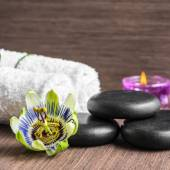 beautiful spa concept of passiflora flower, black zen stones, pu