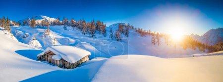 冬季景观在阿尔卑斯在夕阳与旧的山间小屋