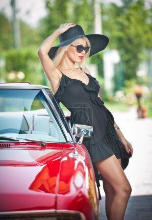 夏天的长长的腿,造成附近红色复古车时尚复古美女的画像。时尚迷人金发女性,黑色的帽子,附近一辆红色的车。阳光明亮的颜色,在户外拍摄._高清图片_邑石网
