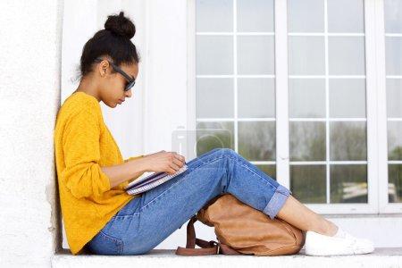 年轻女子坐在户外,读一本书