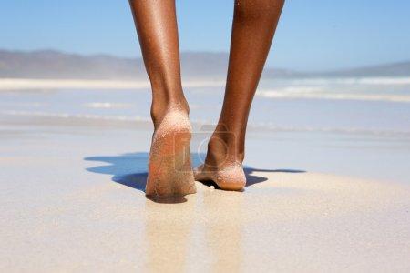 赤脚走在海滩上的女人