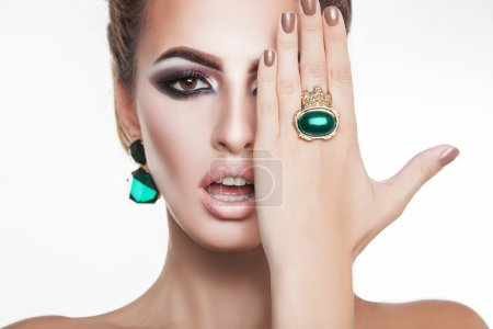 Attractive young woman with green diamonds in accessories lookin