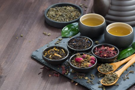 assortment of fragrant dried teas and green tea on dark wooden t