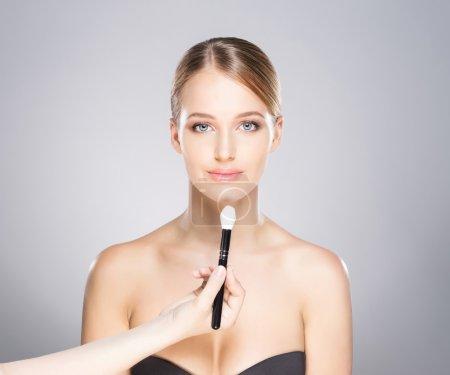 漂亮的女孩是被应用与化妆品