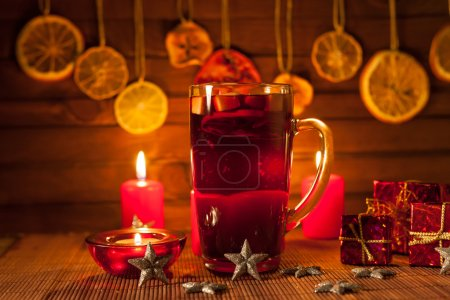 Glass of mulled wine and Christmas decorations, candles, gifts on linen background