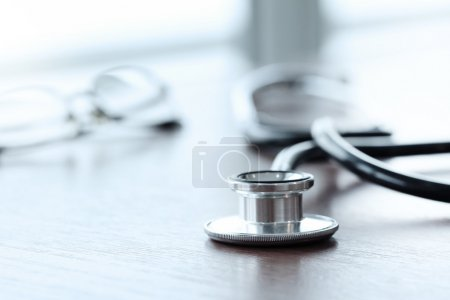 Stethoscope with digital tablet computer on wooden table and  ba