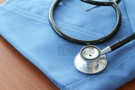 Stethoscope with blue doctor coat on wooden table and  backgroun