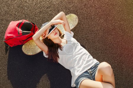 Woman lying on the ground with skateboard and backpack