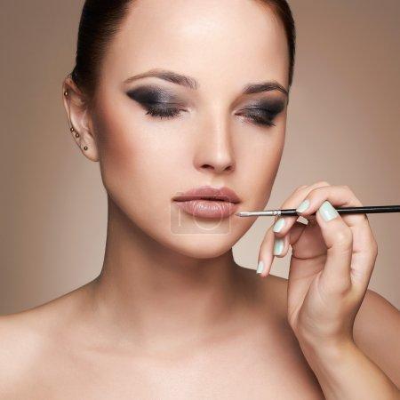 美丽的女人的脸女孩与完美的化妆。化妆师适用口红