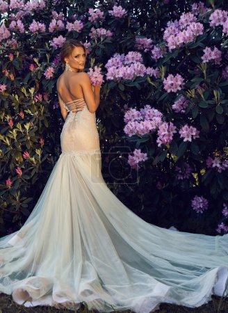 美丽的金发新娘在花园里的豪华婚纱