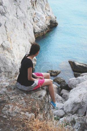 女孩在悬崖上,看着蓝色的水