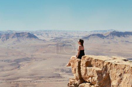 女孩看着沙漠景观的悬崖上